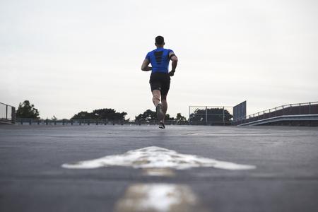 カメラから離れた道を走る男性アスリート、全長