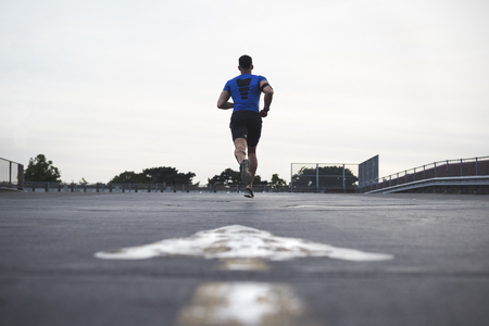 Male athlete running on a road away from camera, full length