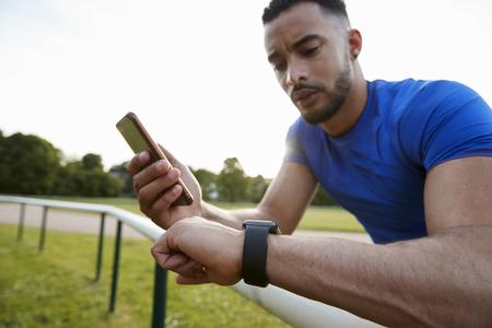 スマートフォンやスマートウォッチでフィットネスアプリを使用して男性アスリート