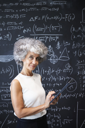 Middle aged academic woman at blackboard smiling to camera