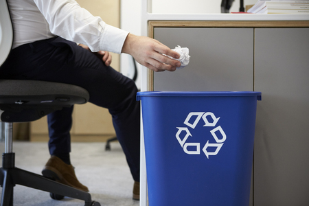 Man dropping screwed up paper into recycling bin, close up Stock Photo