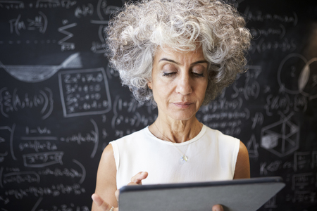 Middle aged academic woman using tablet, close up