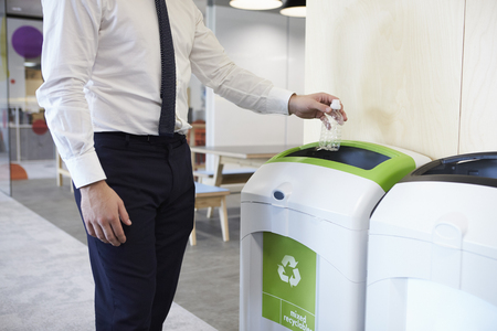 Man in an office throwing plastic bottle into recycling bin 스톡 콘텐츠