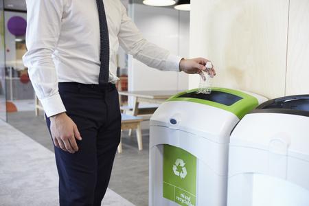 Man in an office throwing plastic bottle into recycling bin Stockfoto