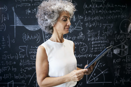 Middle aged academic woman working at blackboard Imagens