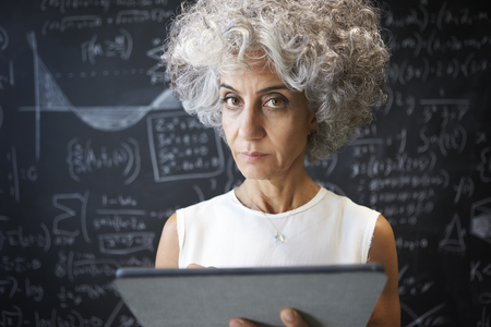 Middle aged academic woman using tablet looking to camera Imagens