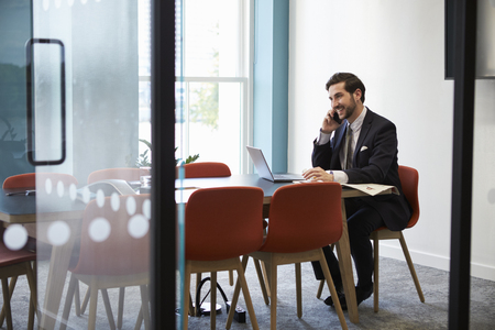 Young businessman making a phone call in a boardroom Stock Photo
