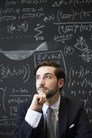 Young man contemplaiting in front of blackboard Imagens