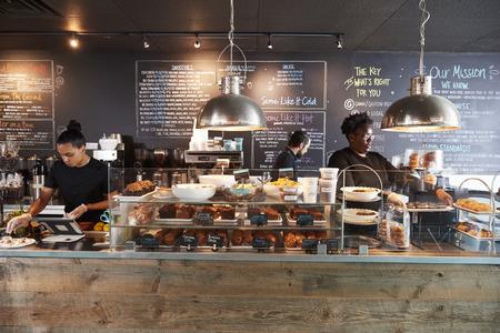 忙しいコーヒーショップでカウンターの後ろで働くスタッフ