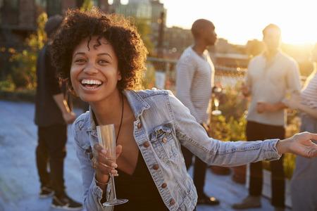 屋上パーティーで踊る若い女性がカメラに微笑む