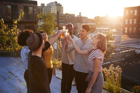 Friends make a toast at a rooftop party, backlit by sunlight Stockfoto