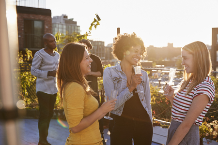 Female friends talking at a rooftop party, backlit Stock Photo