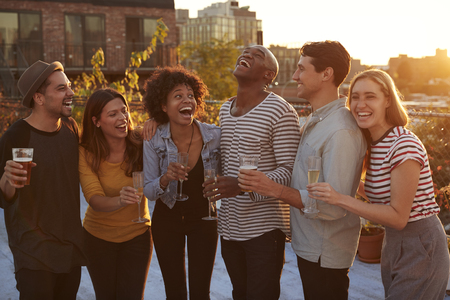 Friends drinking and laughing at a rooftop party in Brooklyn