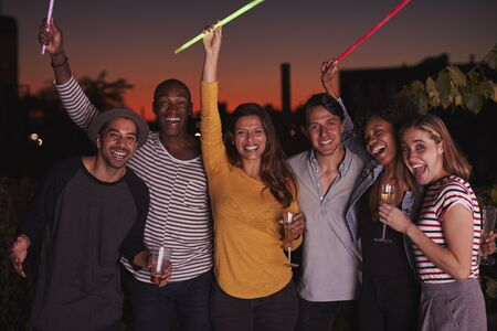 Adult friends waving glowsticks at rooftop party in Brooklyn Stok Fotoğraf
