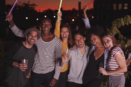 Happy friends waving glowsticks at rooftop party in Brooklyn Stok Fotoğraf