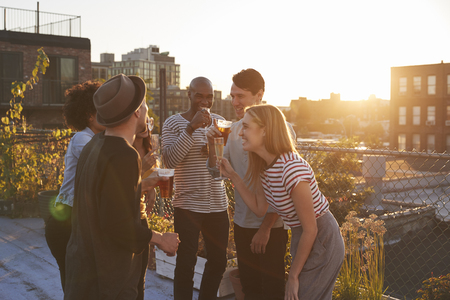 Friends stand talking at rooftop party, backlit by sunlight Stock Photo - 92740137