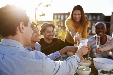Friends making a toast on a New York rooftop, close up