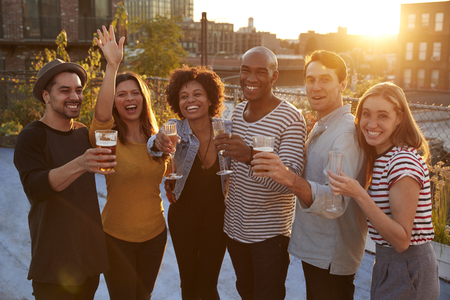 Friends at a rooftop party in raising glasses to camera