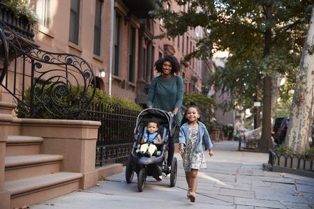 Moeder en twee dochters maken een wandeling door de straat