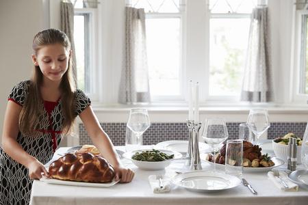 Meisje die challah brood op een lijst plaatsen voor Shabbat-maaltijd