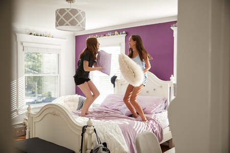 Two girls on a bed having a pillow fight, seen from doorway