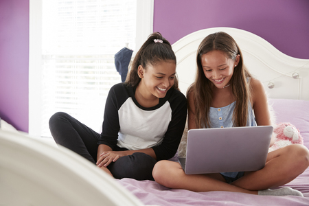 Two teen girls sitting on bed using a laptop, close up