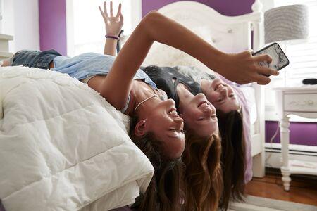 Three teenage girls lying on bed taking a selfie upside down 版權商用圖片 - 93161493