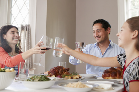 Jewish family raising glasses at the table for Shabbat meal 版權商用圖片