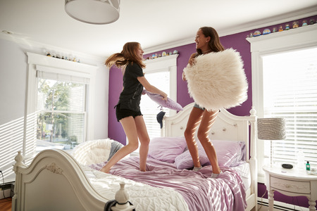 Two teenage girls standing on a bed having a pillow fight Stock Photo