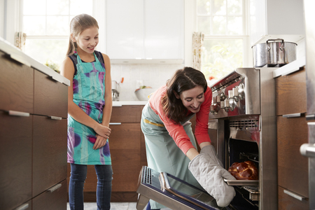 Mother taking bread out of the oven while daughter watches Stock Photo