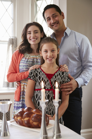 Jewish family smile to camera before Shabbat meal, vertical