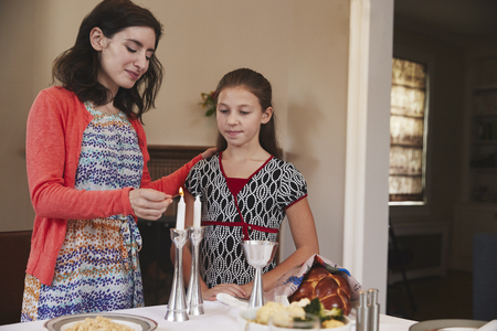 Jewish mother and daughter lighting candles for Shabbat meal Banco de Imagens