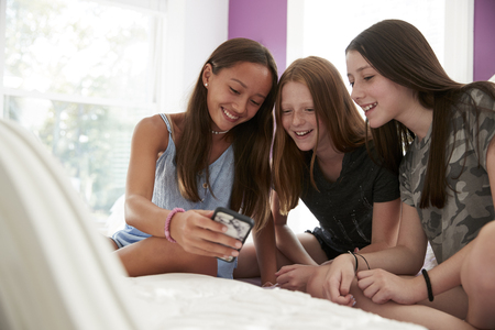 Three girlfriends on a bed using a smartphone, close up Stock Photo