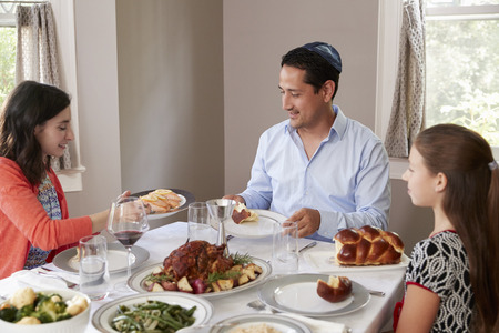Elevated view of Jewish family serving food at Shabbat meal