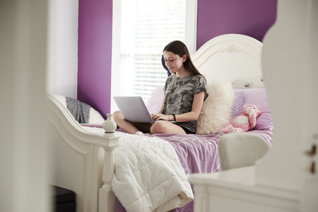Teenage girl sitting on her bed using a laptop computer Stock Photo
