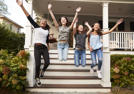Four young teen girls jumping from front steps of a house