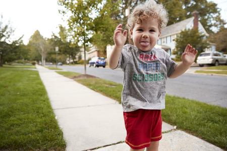 カメラに顔を作る通りに立っている幼児の少年