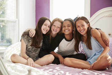 Four teen girls sitting on bed looking at camera, close up Stock Photo