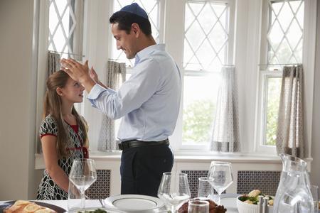 유대인 아버지는 안식일 식사 세트로 딸을 축복합니다.
