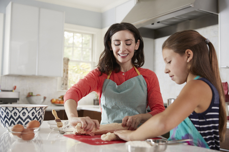 Jewish mother and daughter rolling dough for challah bread 스톡 콘텐츠