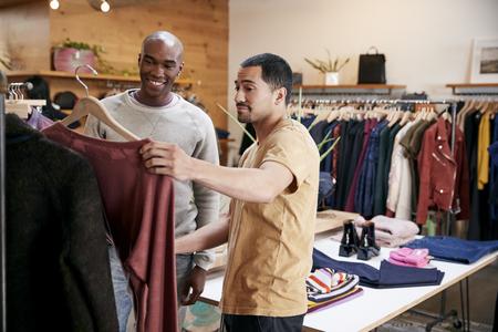 Twee mannelijke vrienden die kleren in een klerenwinkel bekijken