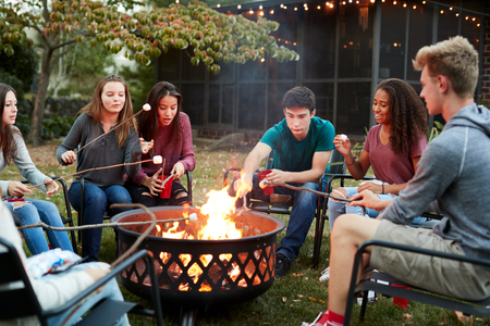 Teenage friends sit round a fire pit toasting marshmallows Stock Photo