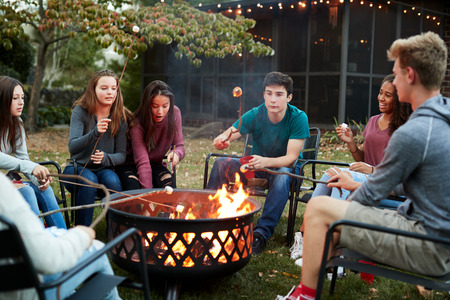 Teenage friends sit round a fire pit toasting marshmallows Imagens