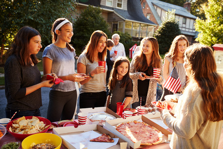 Group of teen girls talking over food table at a block party Archivio Fotografico