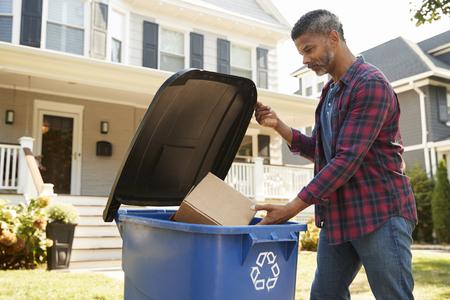 郊外の通りでリサイクルビンを充填する男