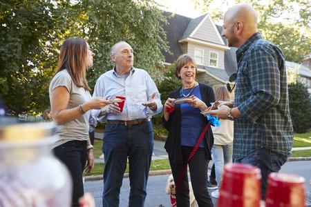 Vicini di mezza età e senior parlando a una festa di blocco Archivio Fotografico - 93401667
