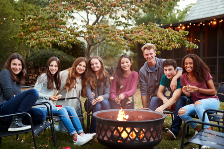Teenage group sitting around a fire pit smiling to camera