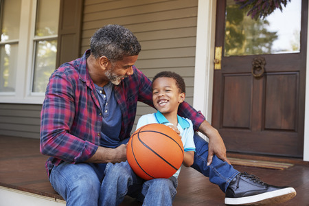 Father And Son Discussing Basketball On Porch Of Home Stok Fotoğraf