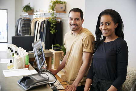 Smiling colleagues behind the counter in clothing store Stock Photo