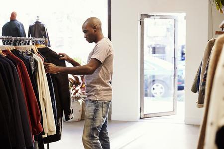 상점에서 레일에 옷을 통해 브라우징 젊은 흑인 남자 스톡 콘텐츠